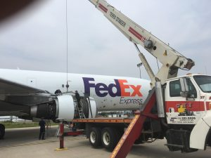 Picture of KC Crane's 35 ton crane holding FedEx Jet Engine for repairs